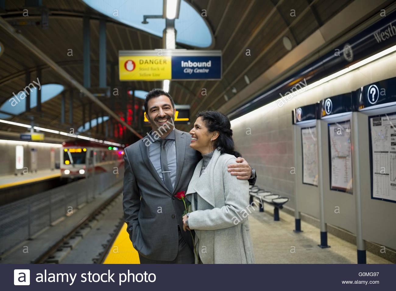 Smiling couple hugging on subway station platform - Stock Image
