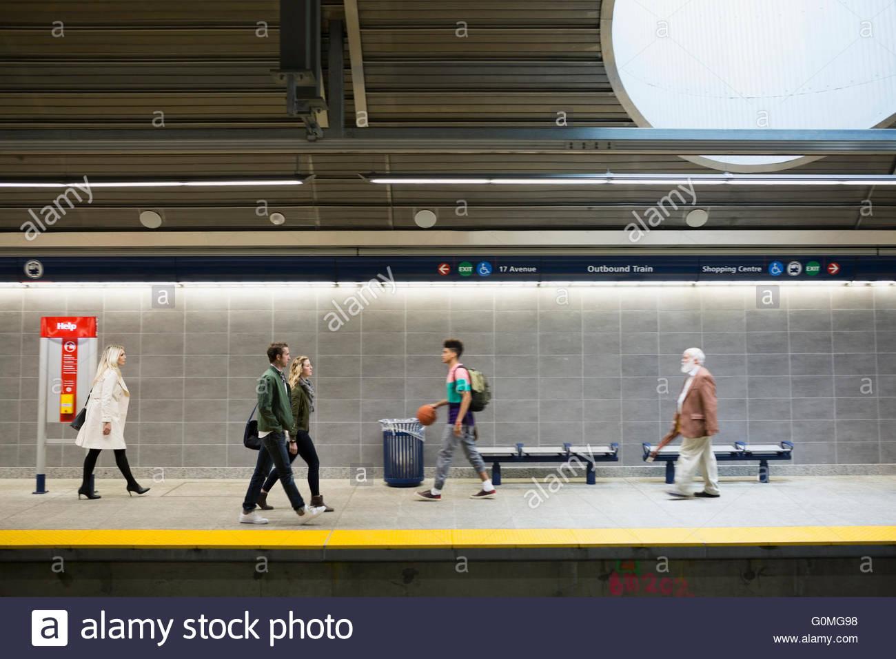 People walking along subway station platform Stock Photo