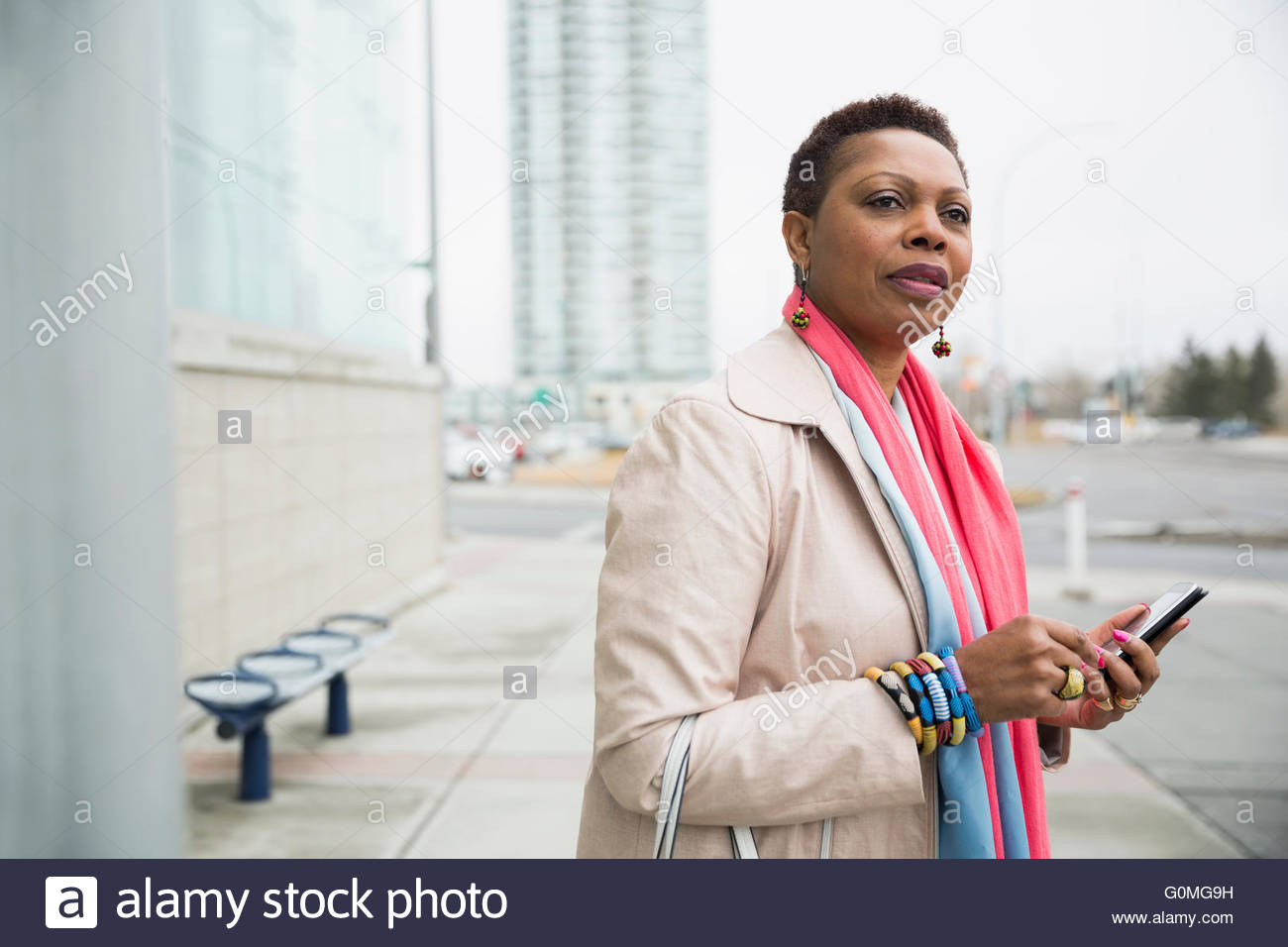 Woman with cell phone waiting at bus stop - Stock Image