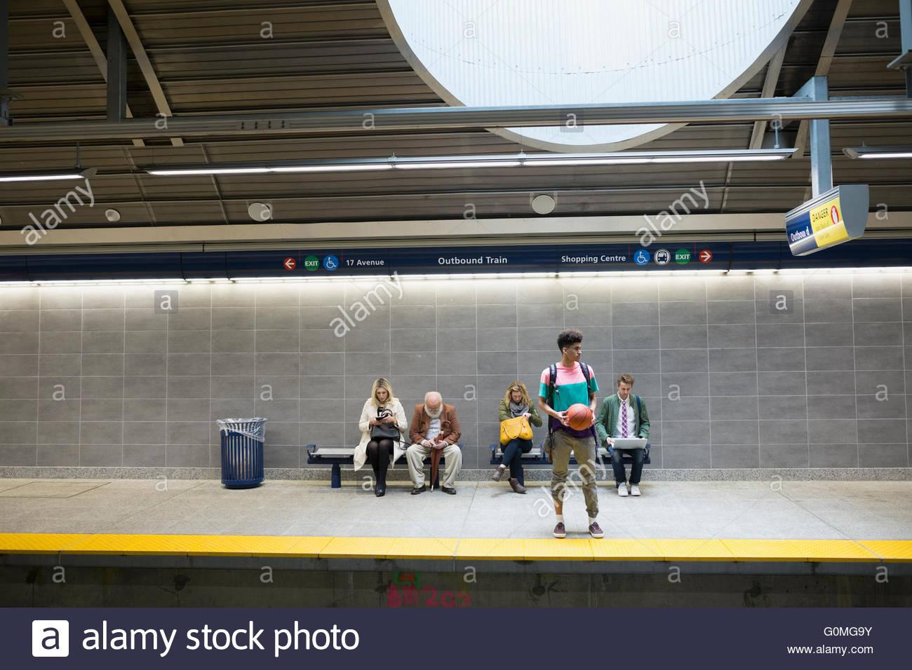 People waiting on subway station platform - Stock Image