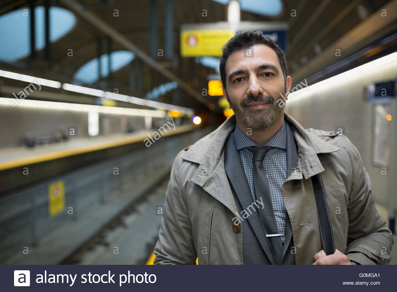 Portrait confident businessman on subway station platform - Stock Image
