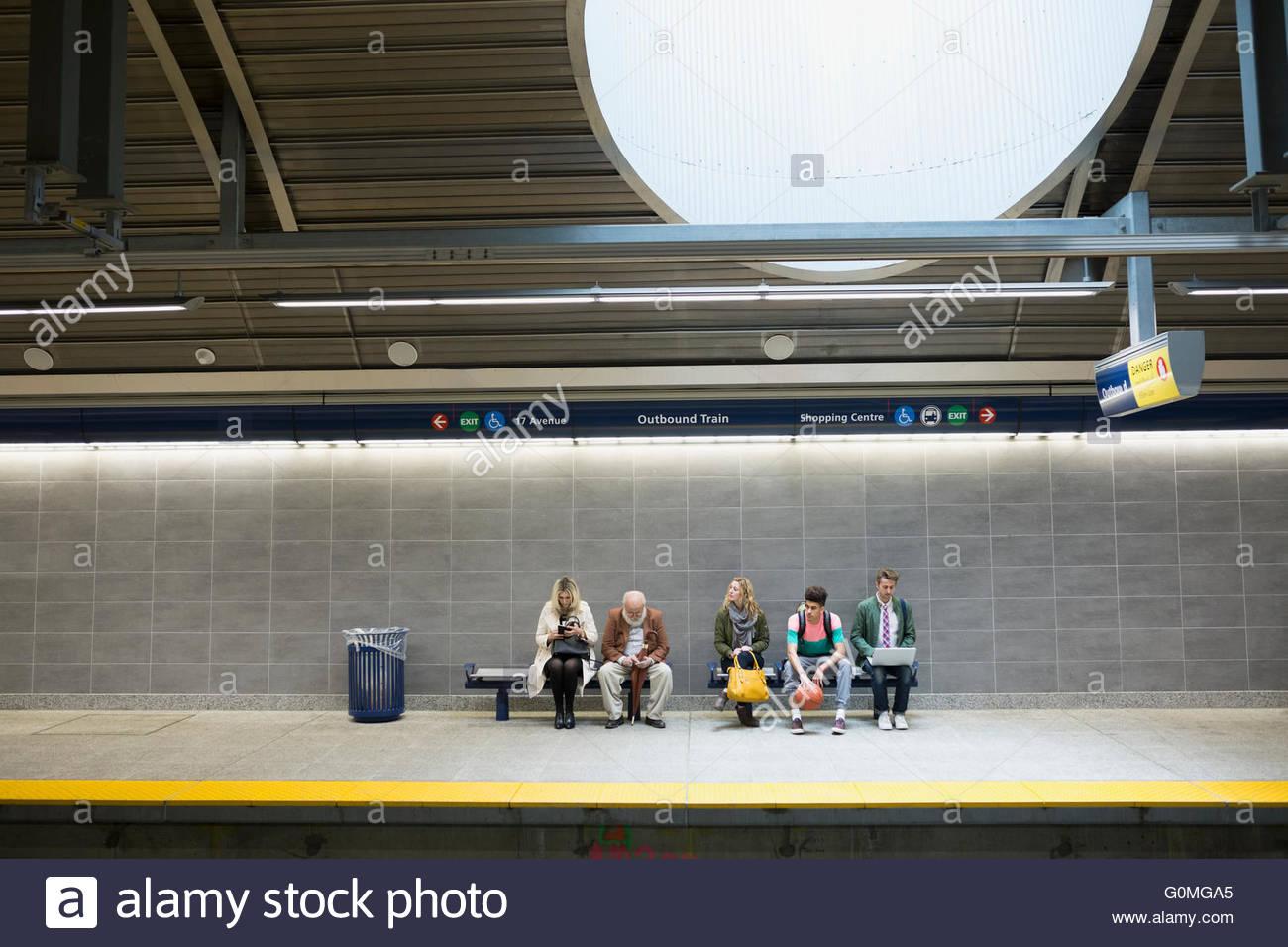 People waiting on benches on subway station platform - Stock Image