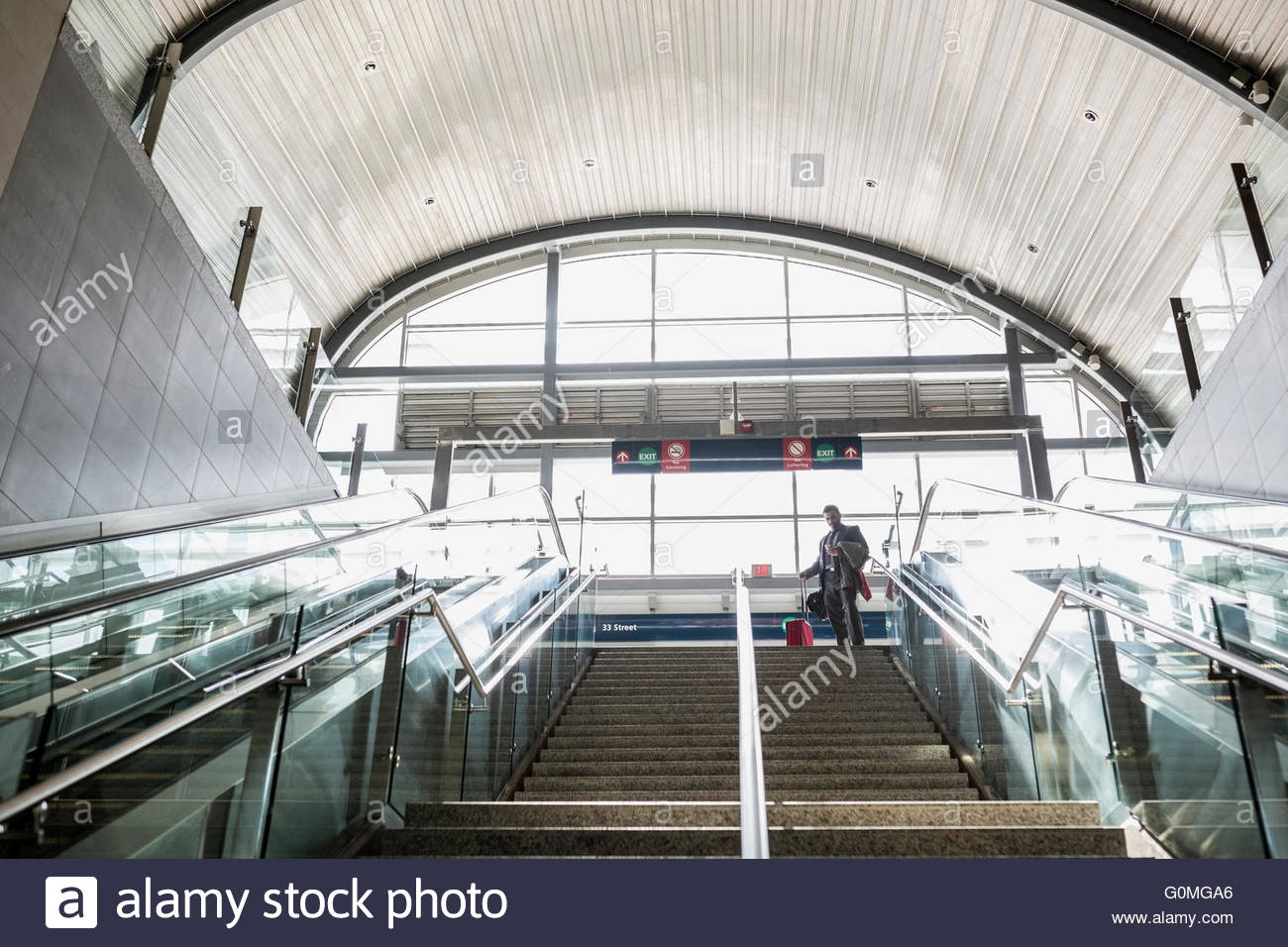 Businessman with suitcase top of stairs train station - Stock Image