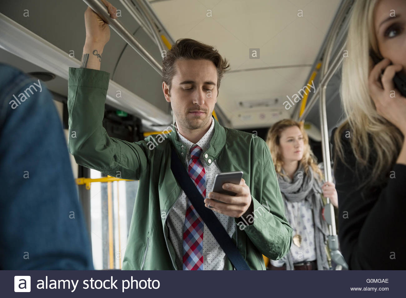 Businessman texting with cell phone standing on bus - Stock Image