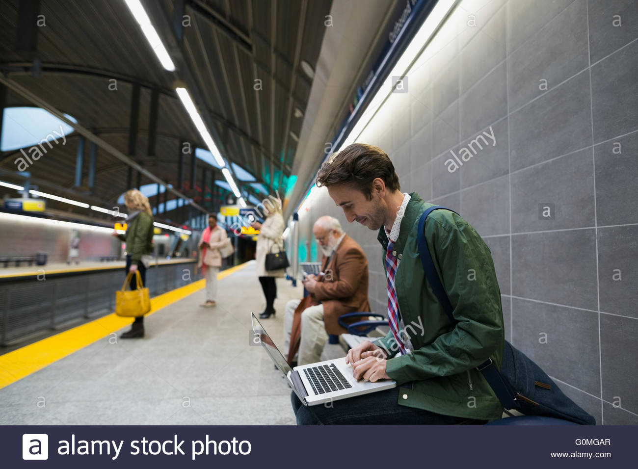Businessman using laptop on bench subway station platform - Stock Image