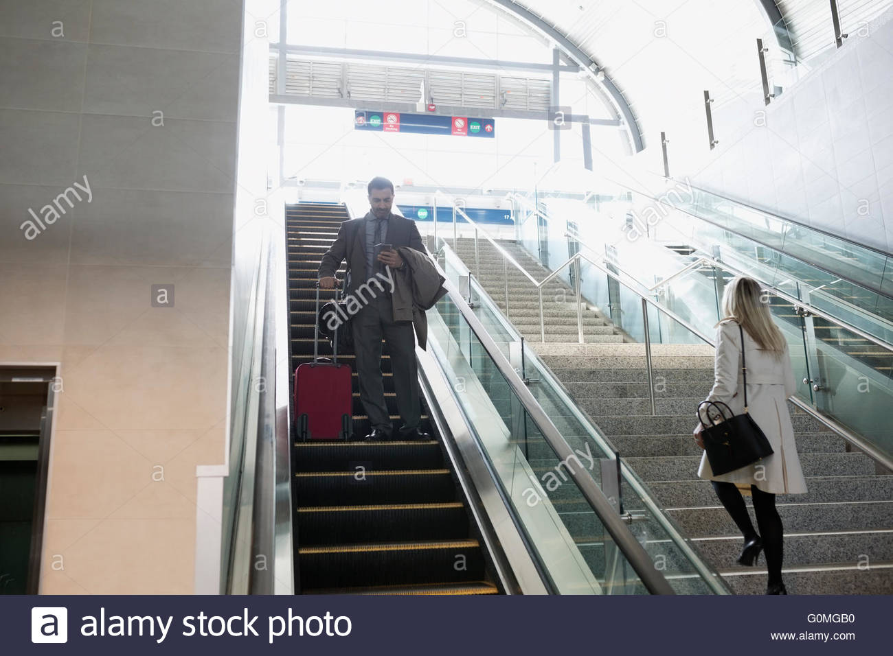 Businessman with suitcase descending escalator at train station - Stock Image