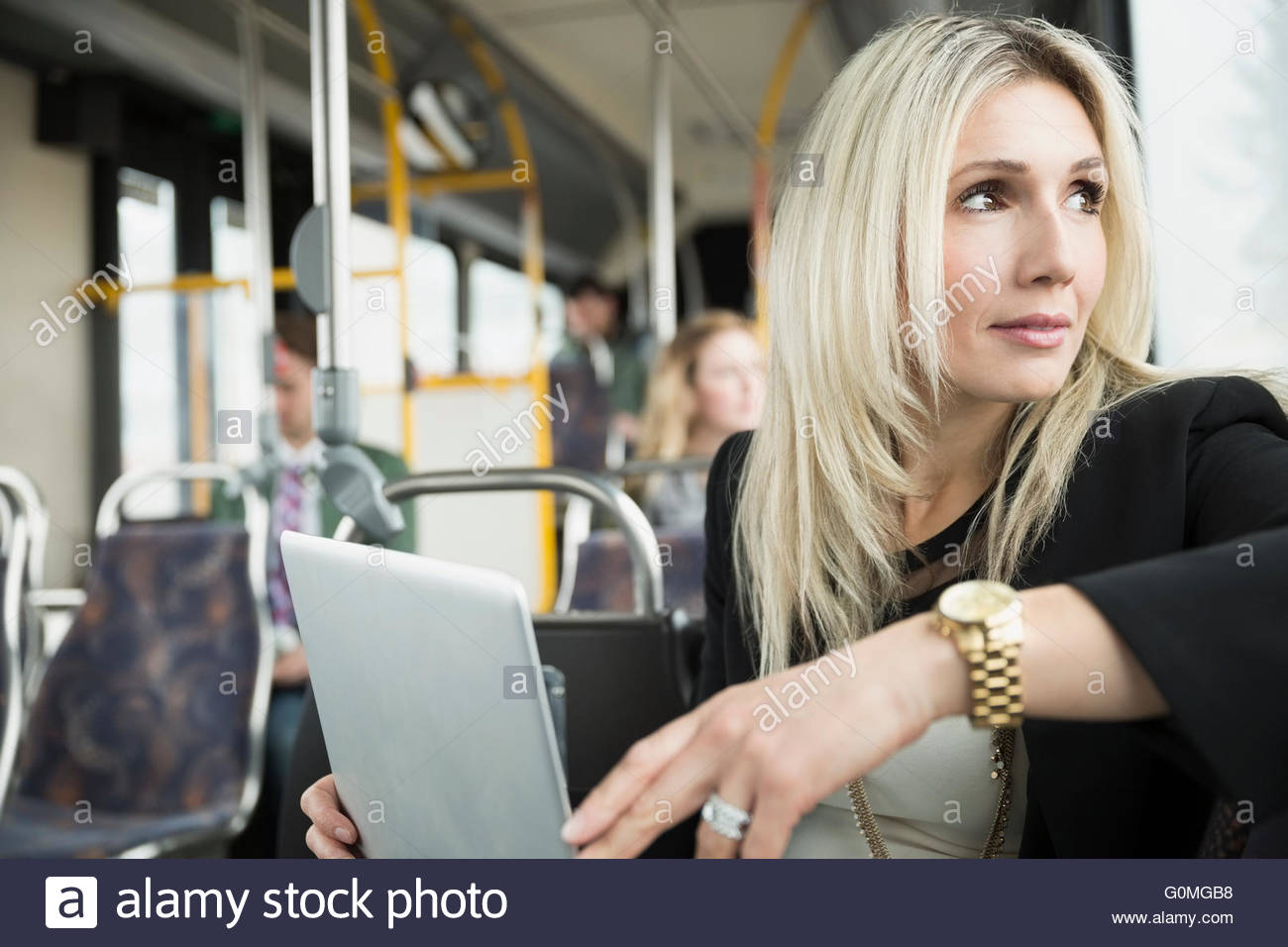 Pensive businesswoman using laptop on bus looking away - Stock Image