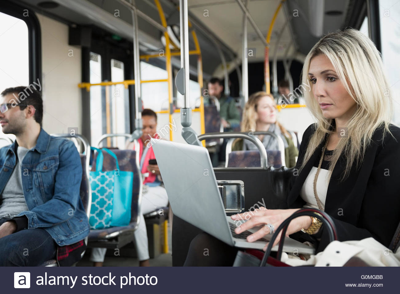 Businesswoman using laptop on bus - Stock Image