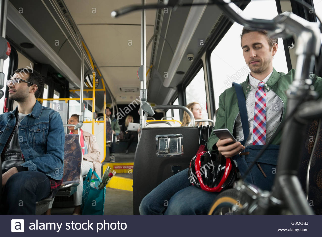 Businessman with bicycle texting on bus - Stock Image