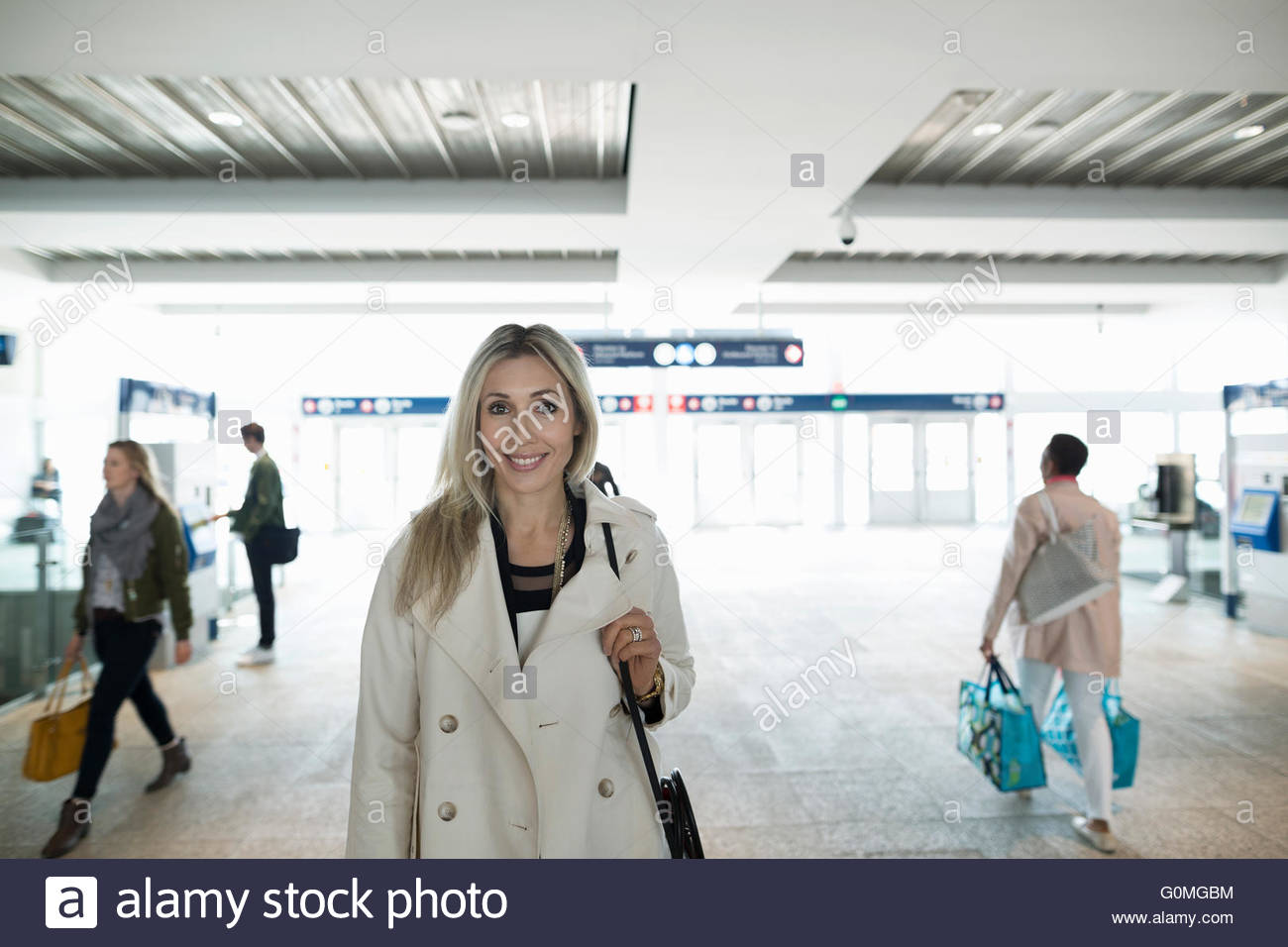 Portrait woman standing in train station entrance - Stock Image