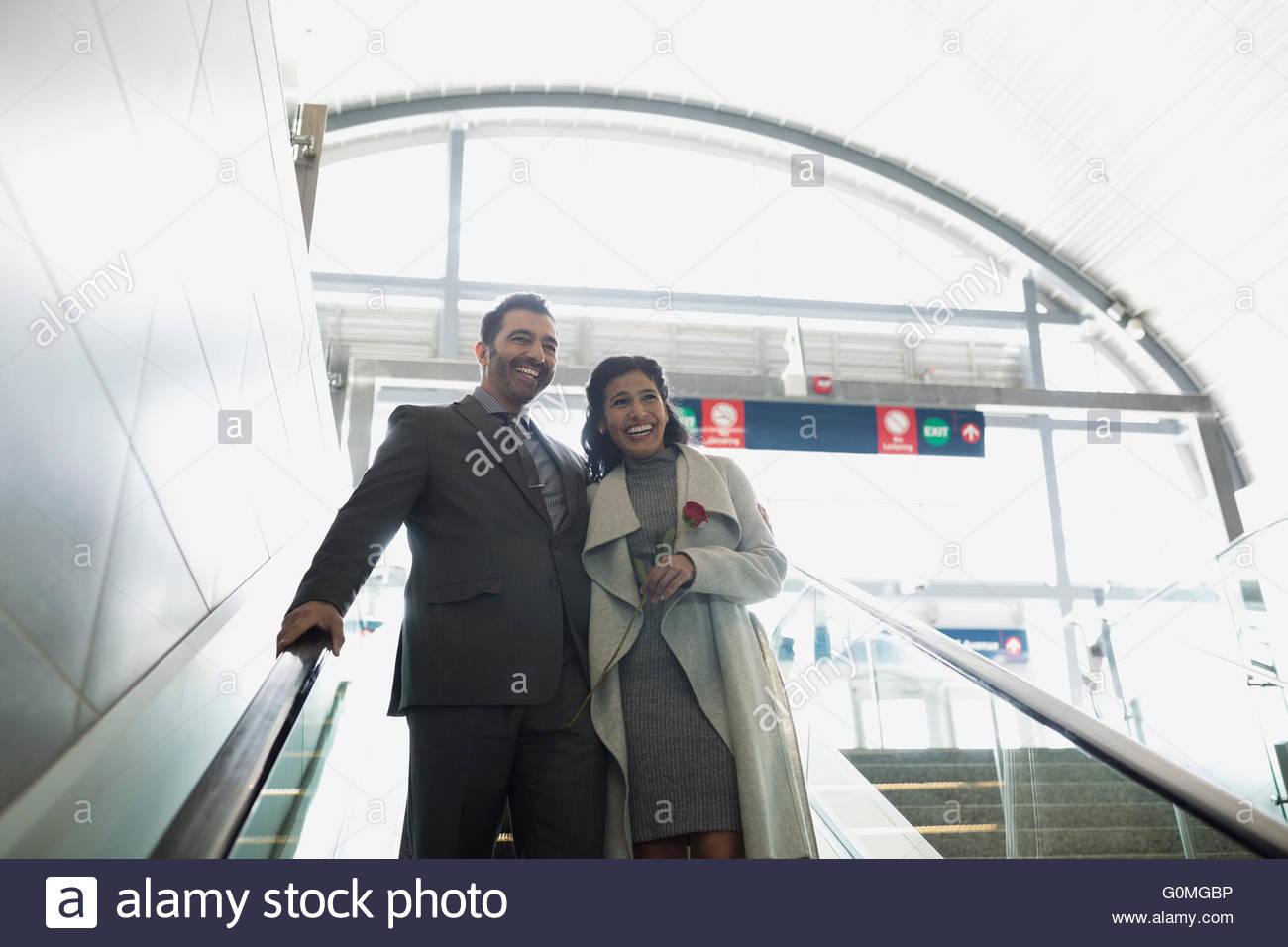 Smiling couple descending escalator at train station - Stock Image