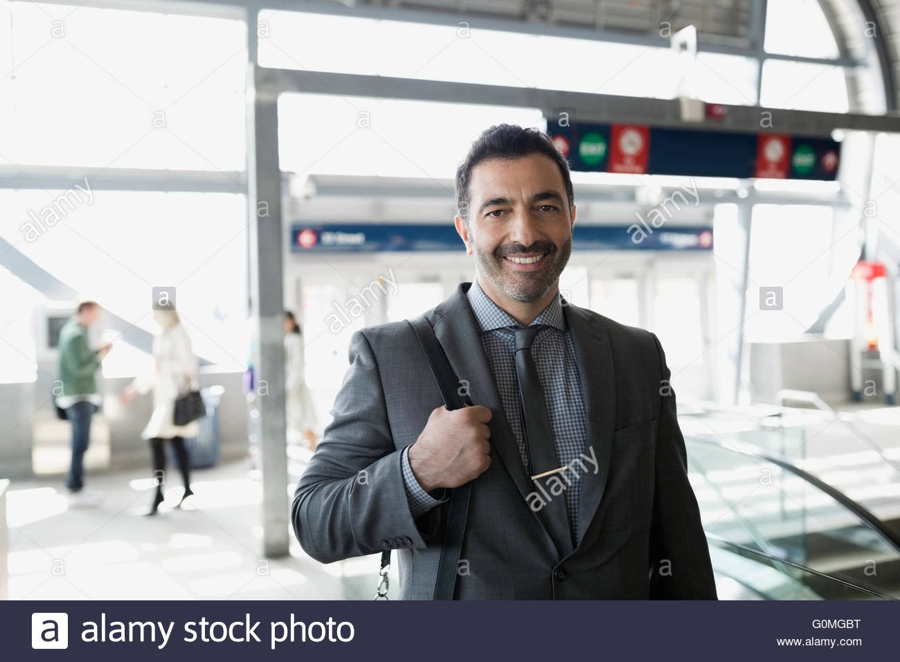 Portrait smiling businessman at train station - Stock Image