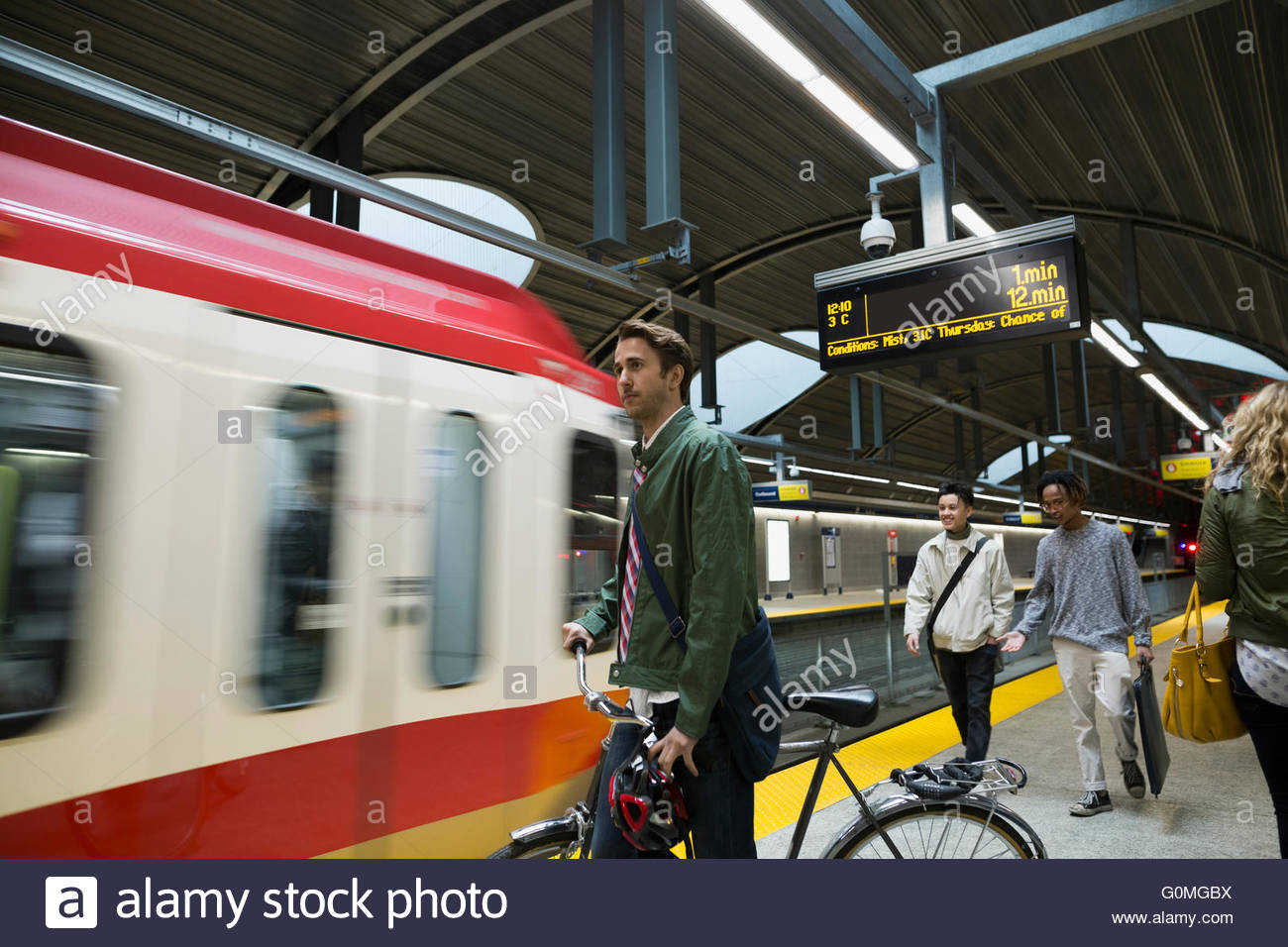 Businessman with bicycle watching arriving subway on platform - Stock Image