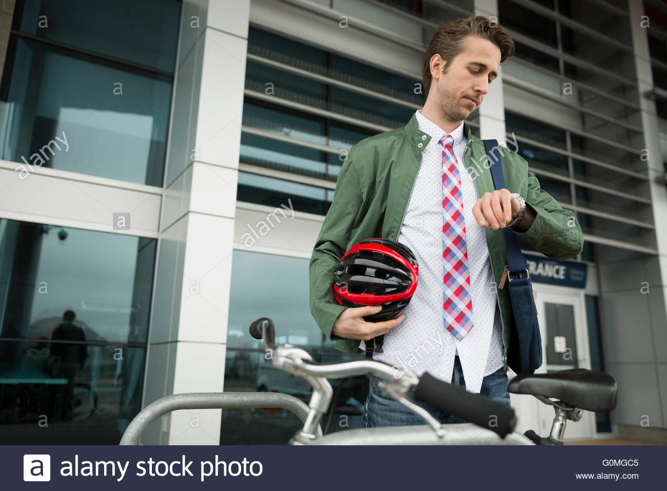 Man with bicycle and helmet checking wristwatch - Stock Image
