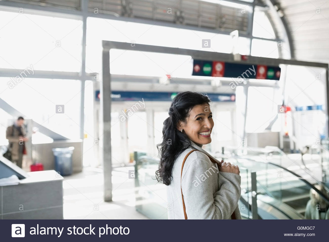 Portrait smiling woman at train station - Stock Image