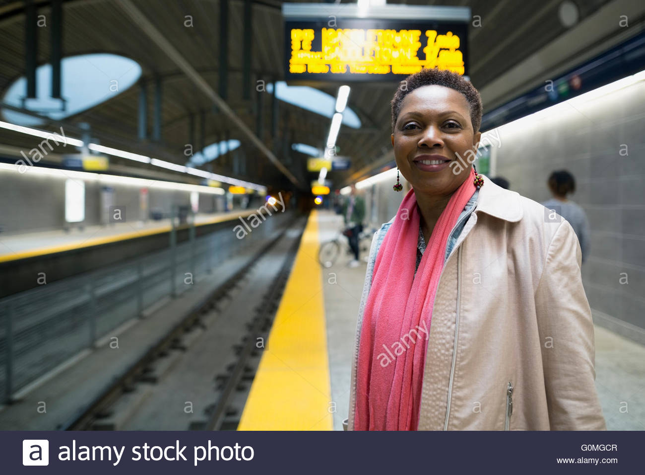 Portrait smiling woman waiting on subway station platform - Stock Image