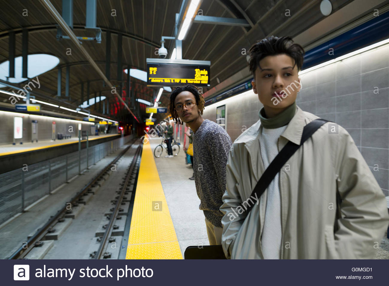 Young men waiting on subway station platform - Stock Image