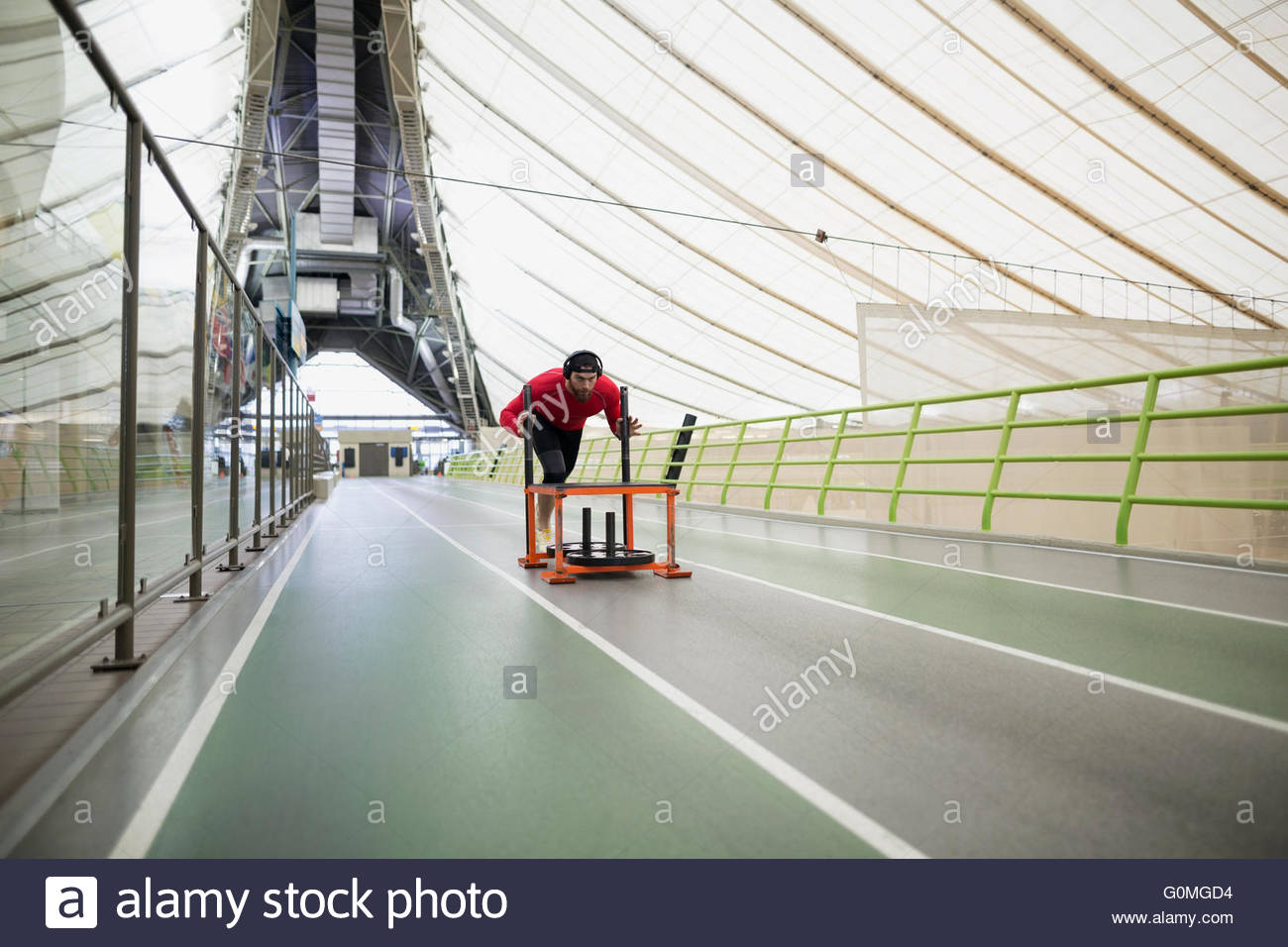 Runner pushing sprinting sled on indoor track - Stock Image