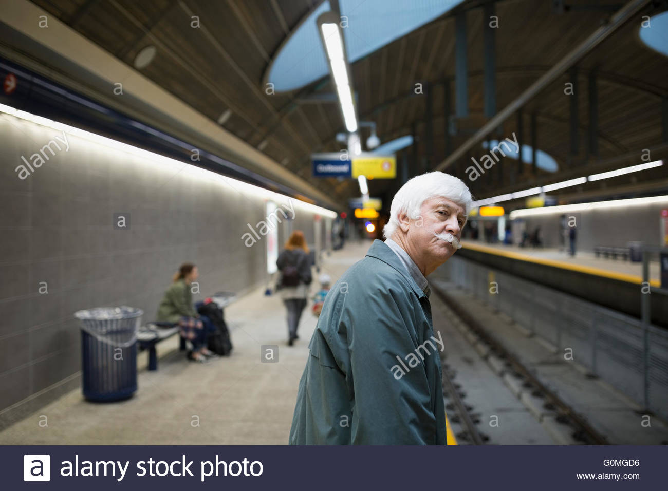 Senior man waiting on subway station platform - Stock Image