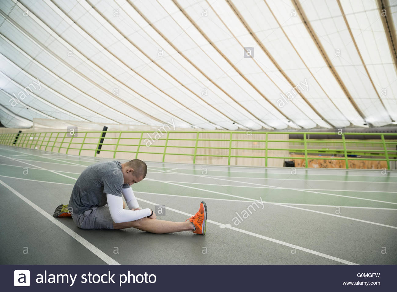 Runner stretching on indoor track - Stock Image