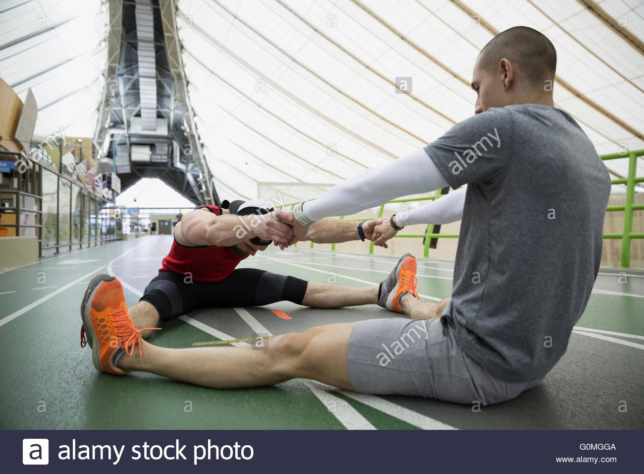 Runners holding hands stretching legs apart indoor track - Stock Image