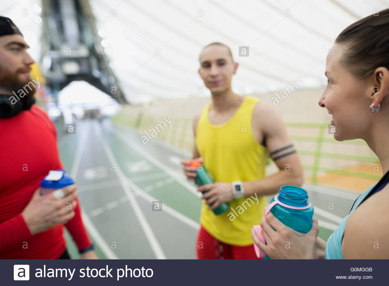 Runners resting talking drinking water on indoor track - Stock Image