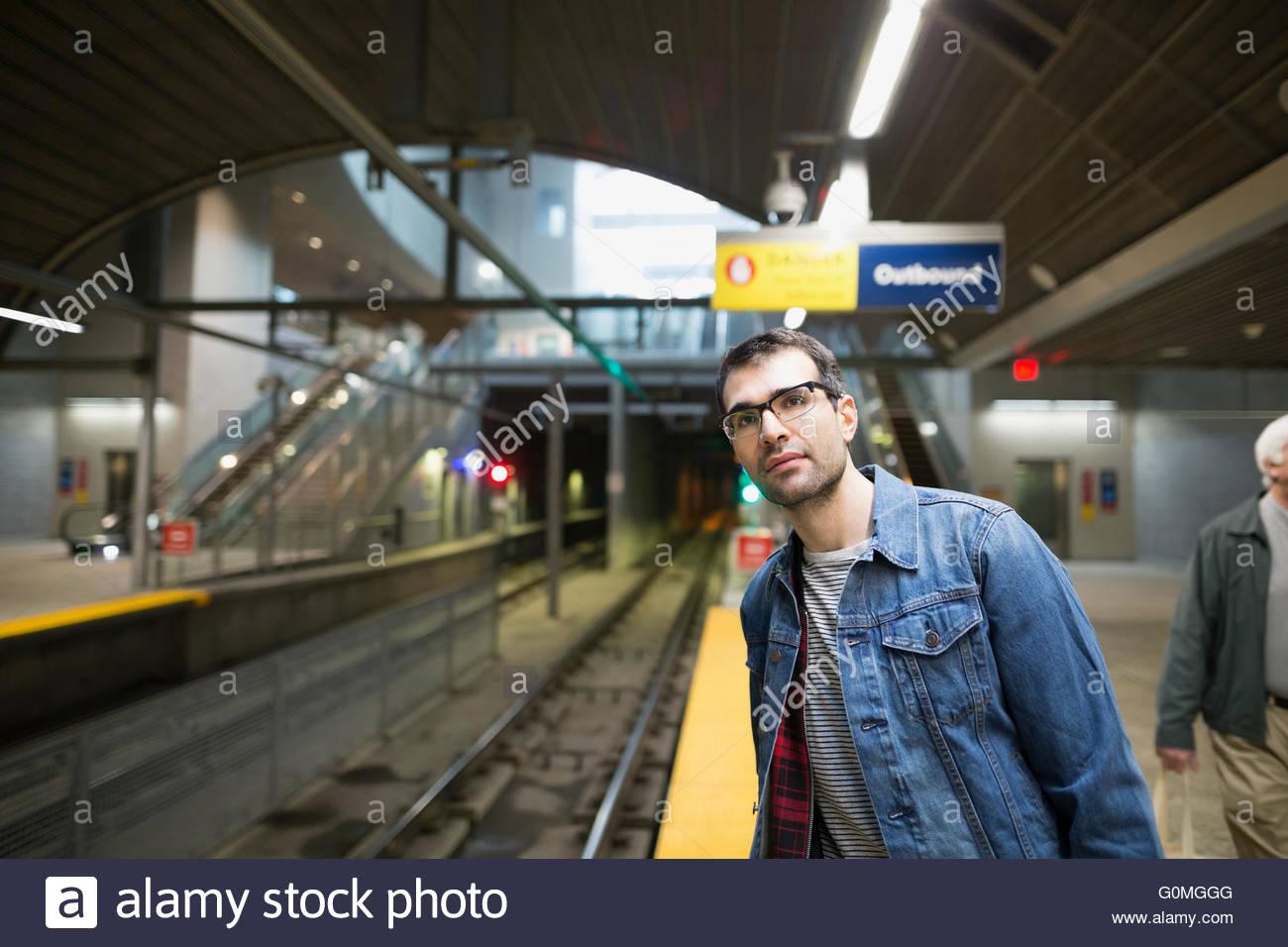 Man in eyeglasses waiting on subway station platform - Stock Image