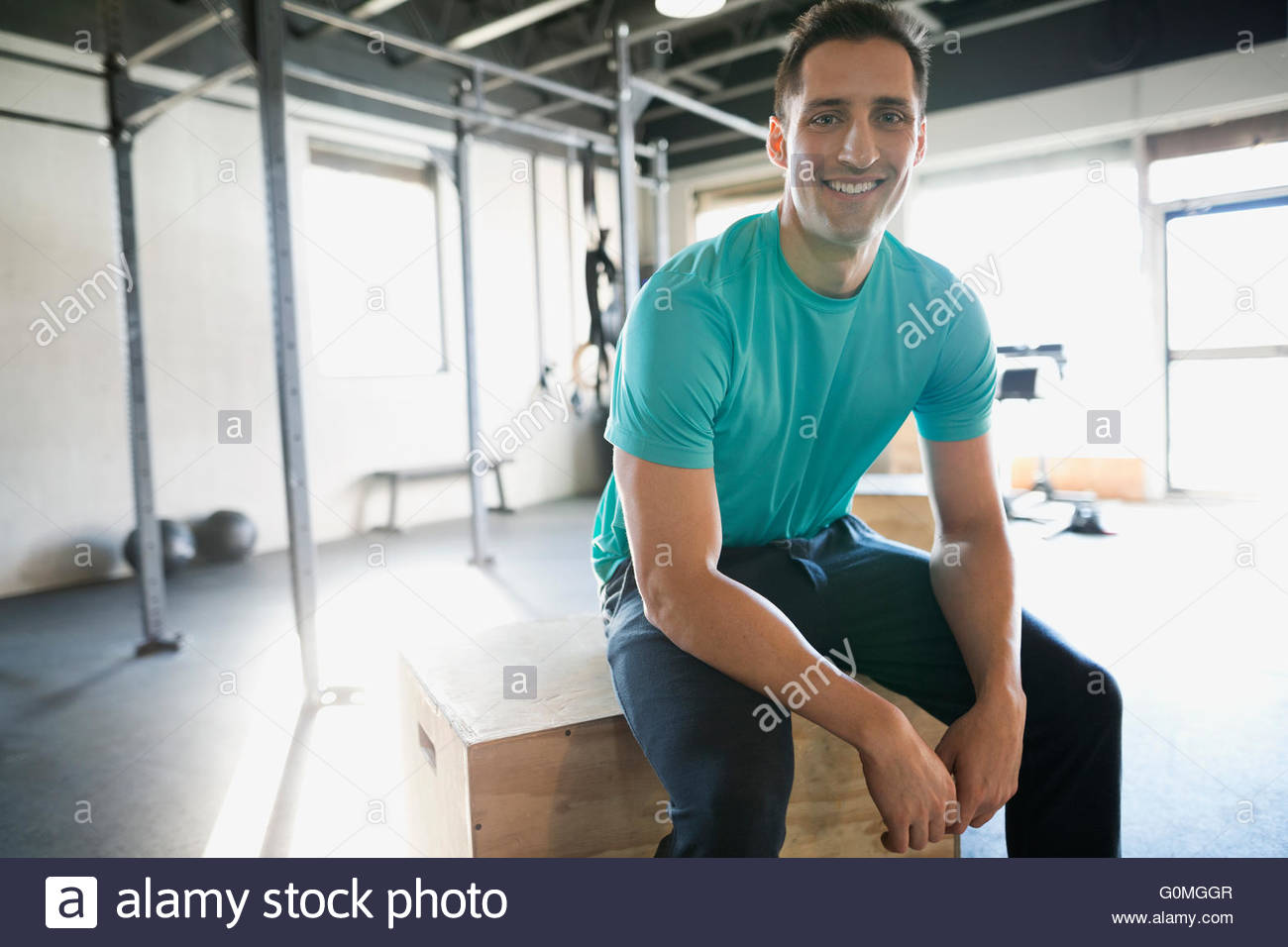 Portrait smiling man resting at gym - Stock Image