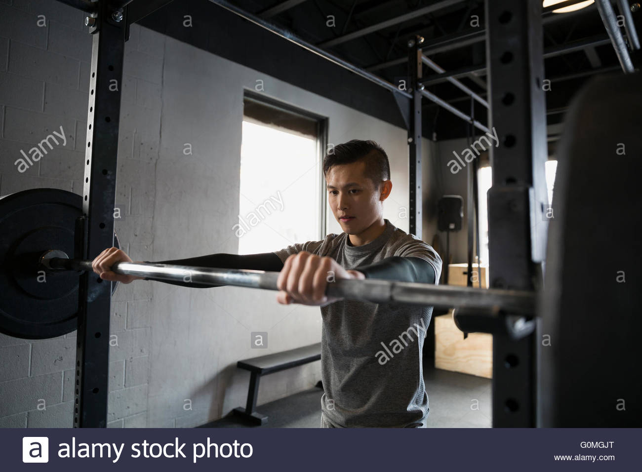 Man at barbell rack at gym - Stock Image