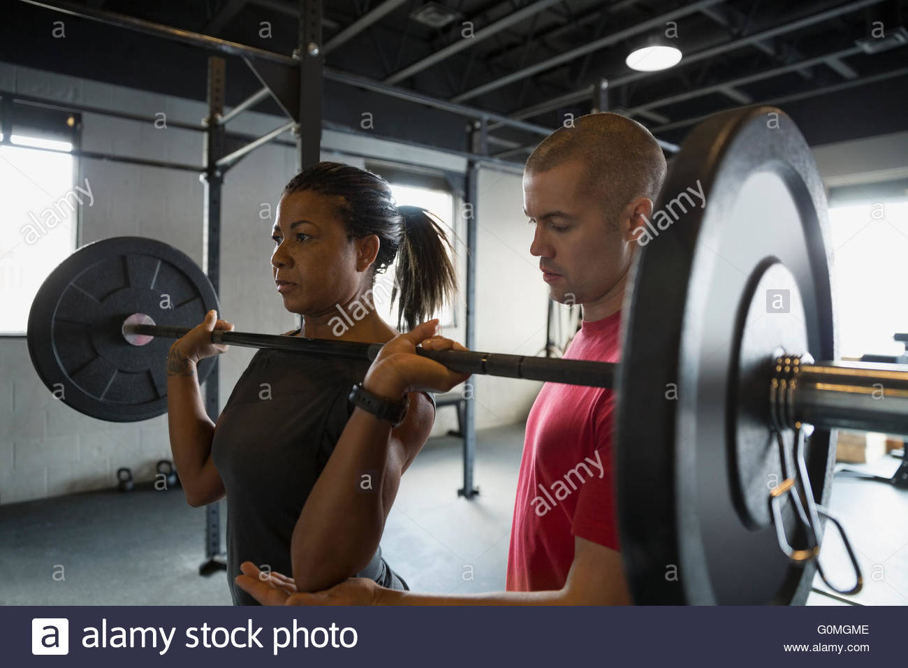 Personal trainer guiding woman weightlifting barbell - Stock Image