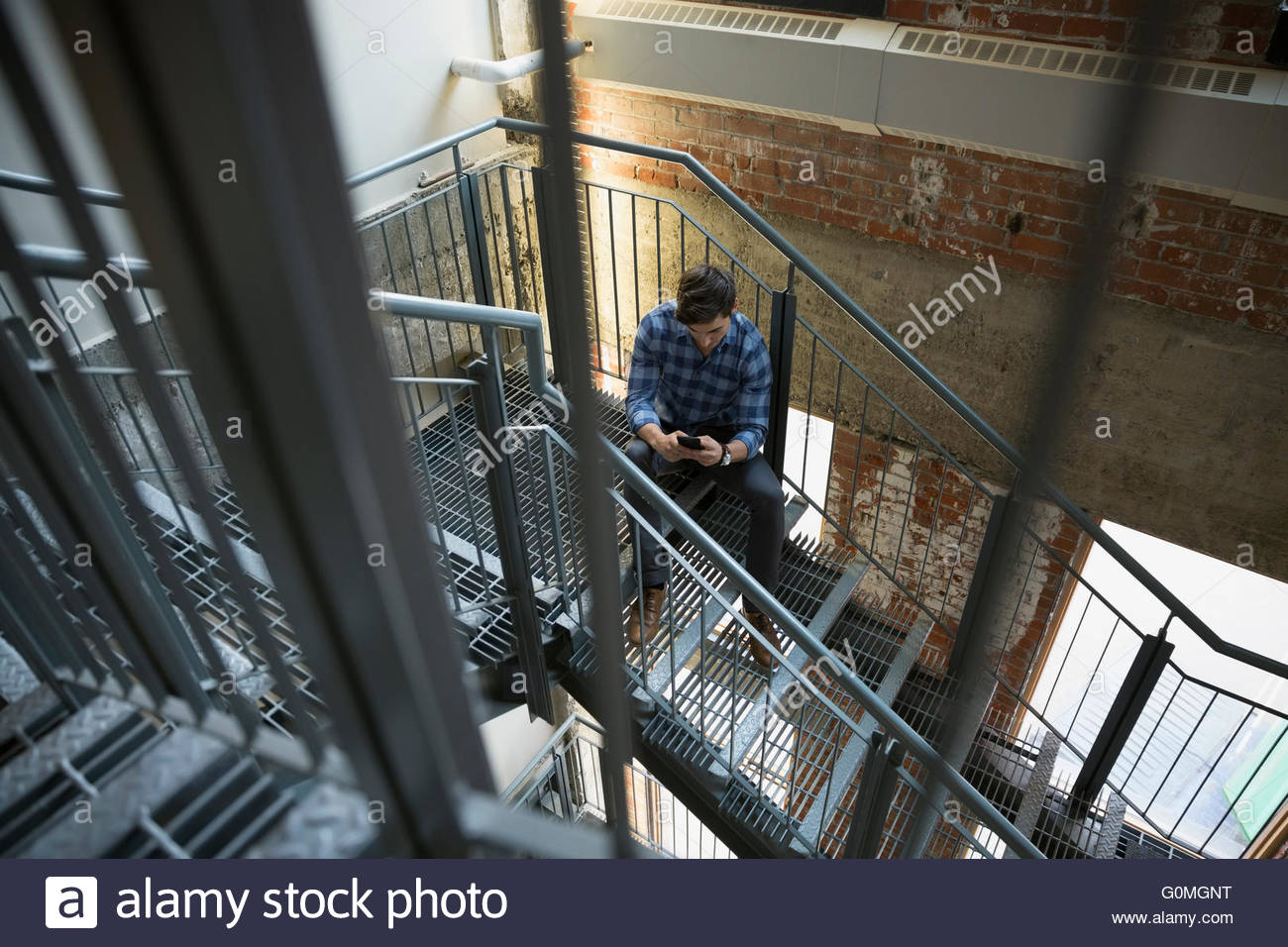 Businessman texting with cell phone in stairwell - Stock Image
