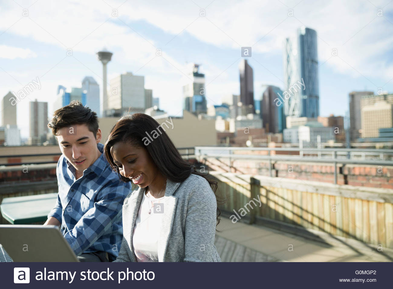 Businessman and businesswoman using digital tablet urban rooftop - Stock Image