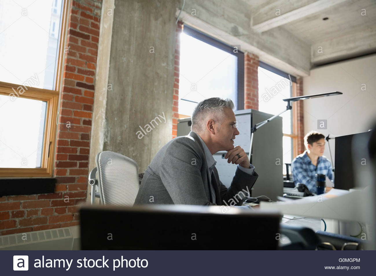 Businessman working at desk in office - Stock Image