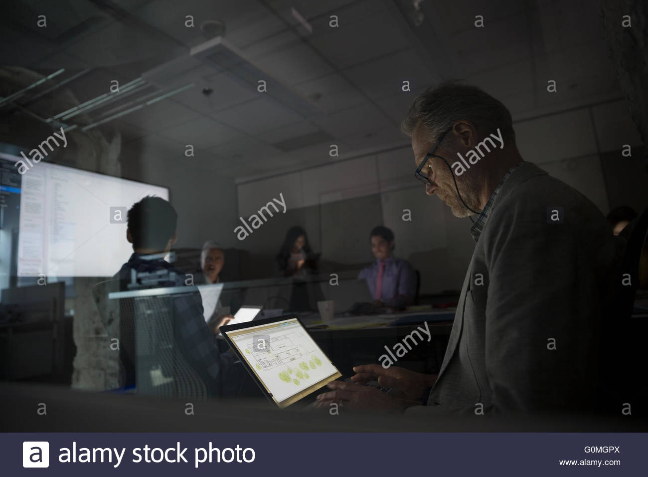 Architect using laptop dark conference room meeting - Stock Image
