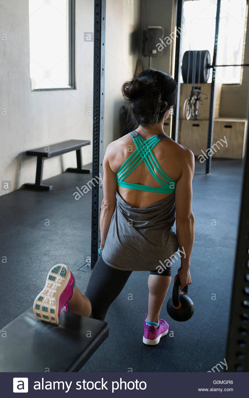 Woman doing one-legged kettlebell lunges gym - Stock Image