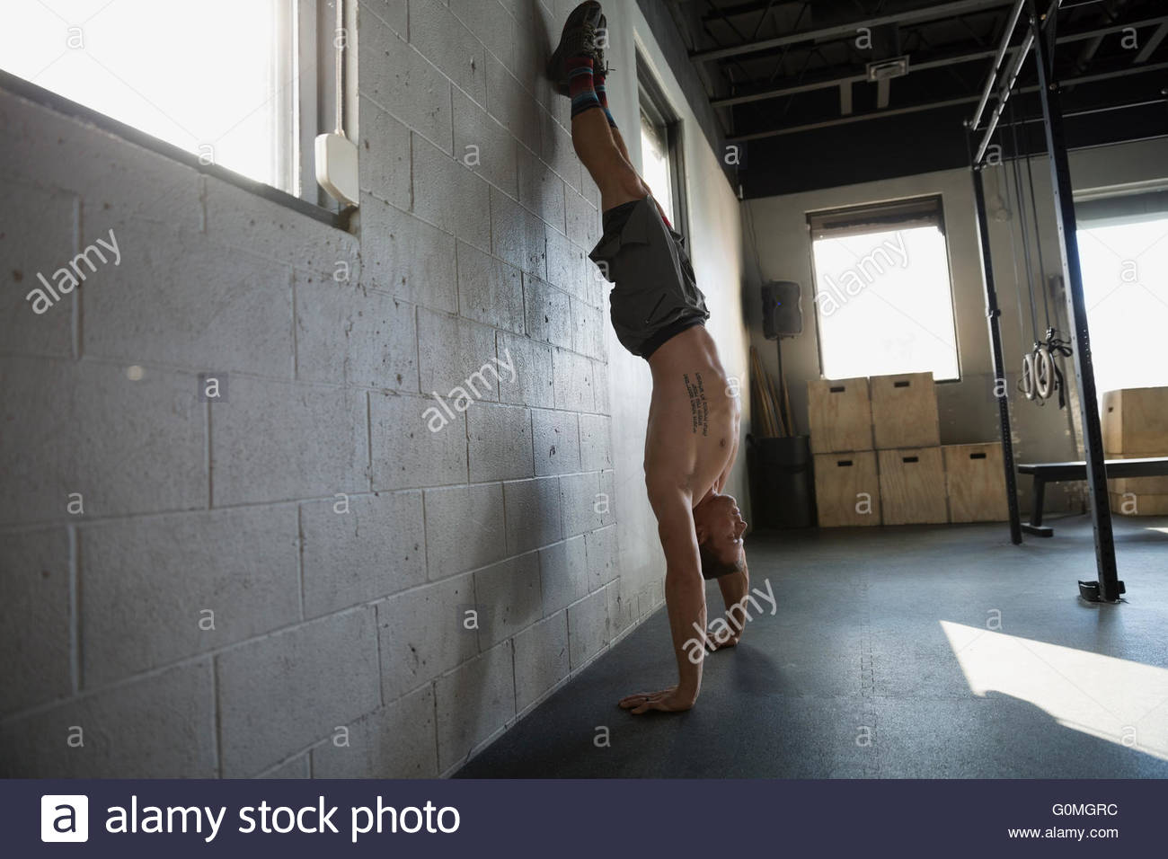 Bare chested man doing handstand at gym wall - Stock Image