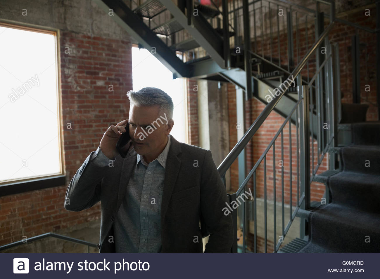 Businessman talking on cell phone in stairwell Stock Photo