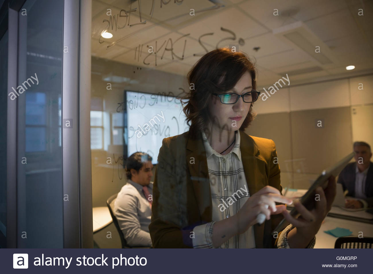 Businesswoman with digital tablet at conference room window - Stock Image