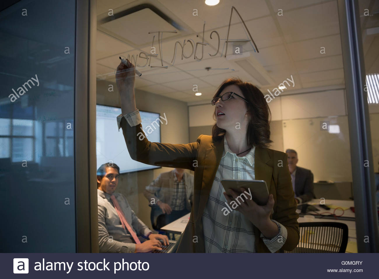 Businesswoman with digital tablet writing on glass - Stock Image