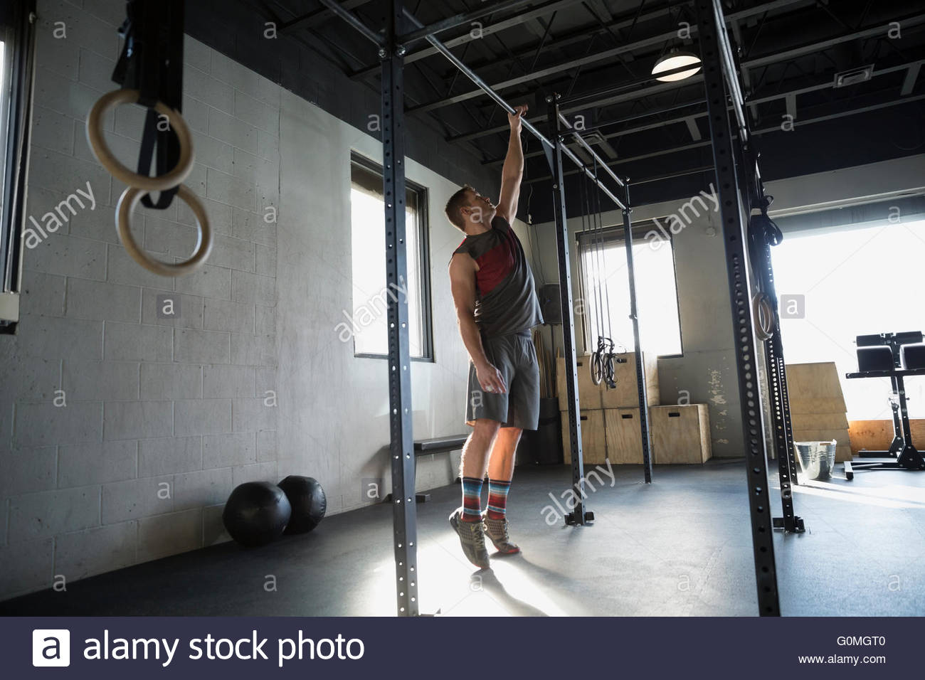 Man doing one-armed pull-ups at gym - Stock Image