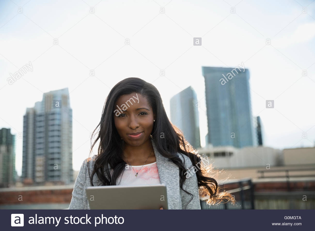 Portrait confident businesswoman using digital tablet urban rooftop - Stock Image