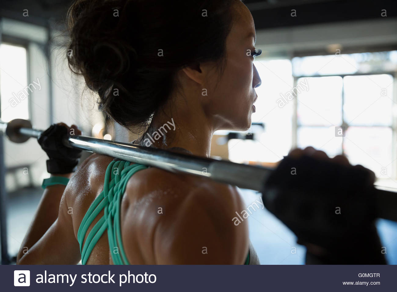 Close up woman weightlifting with barbell at gym - Stock Image