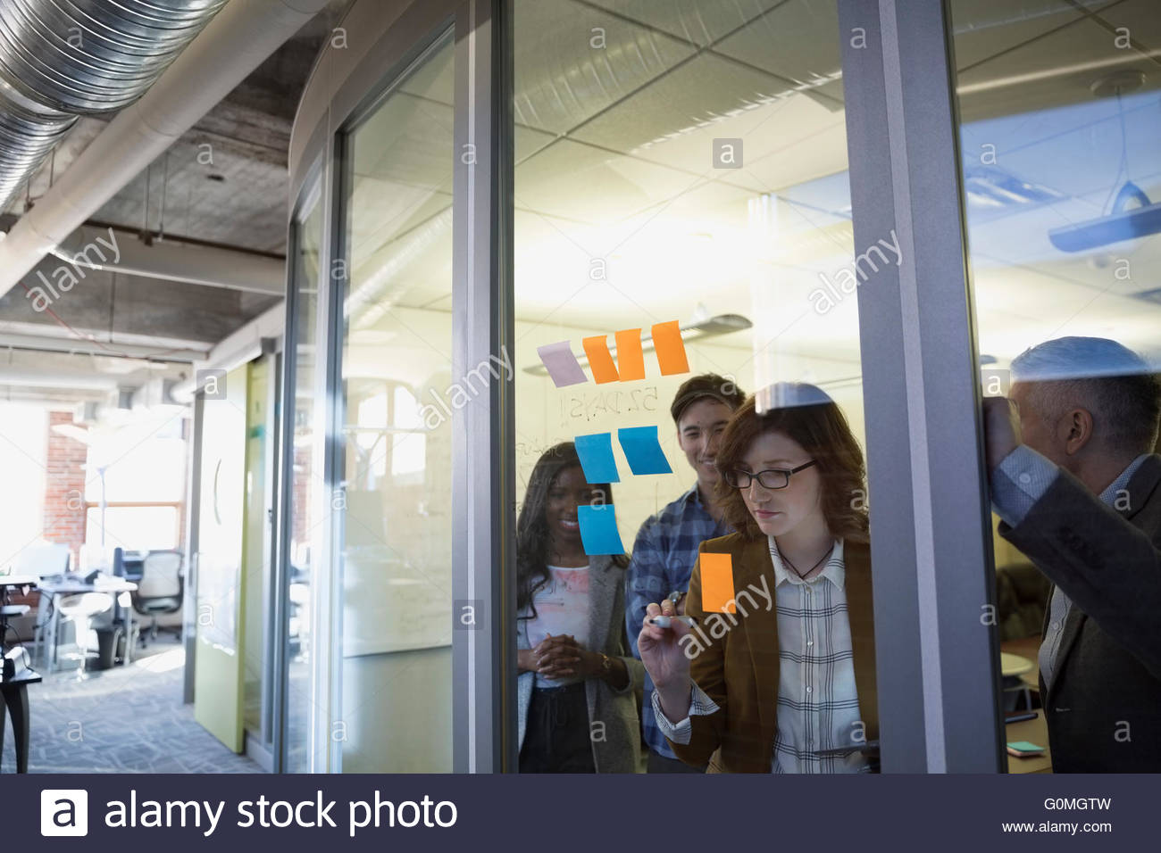 Business people brainstorming with adhesive notes conference room - Stock Image