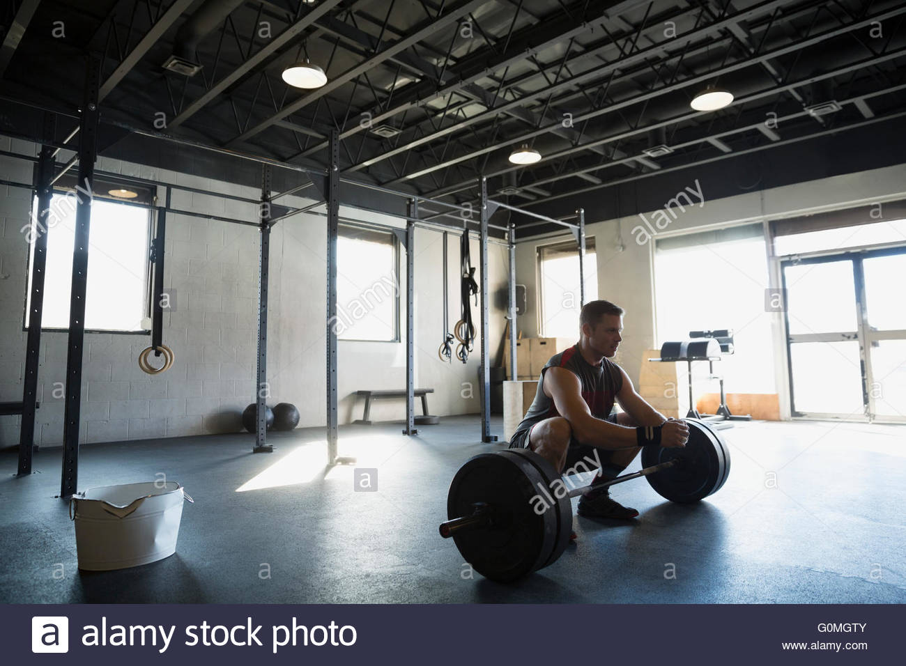 Man squatting over barbell at gym - Stock Image