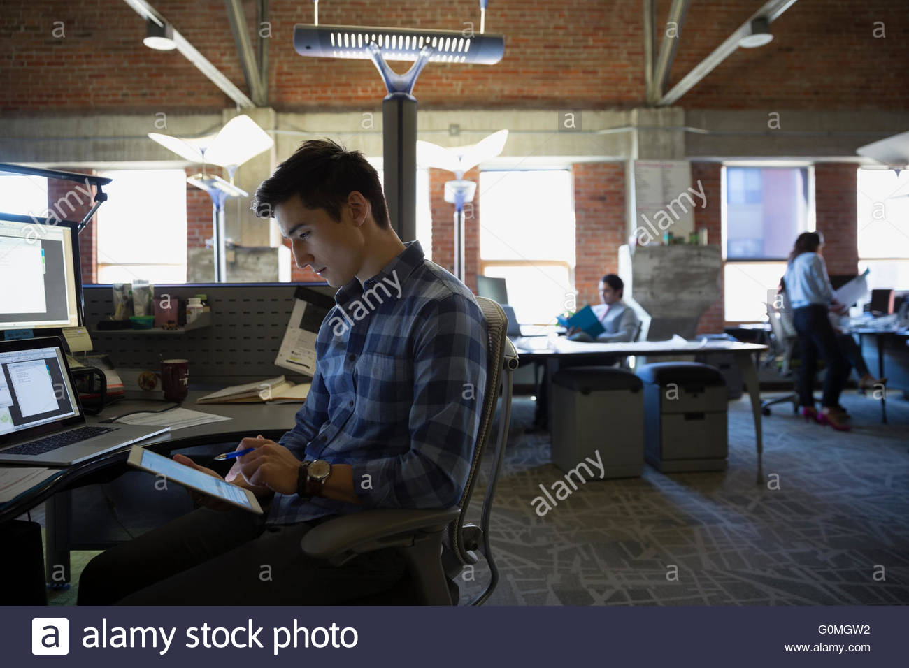 Businessman using digital tablet at desk in office - Stock Image