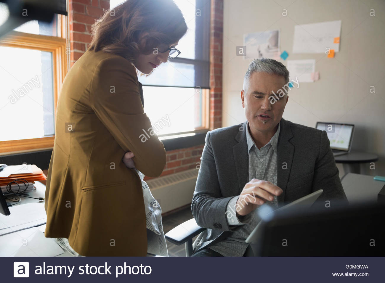 Businessman and businesswoman using digital tablet office desk - Stock Image