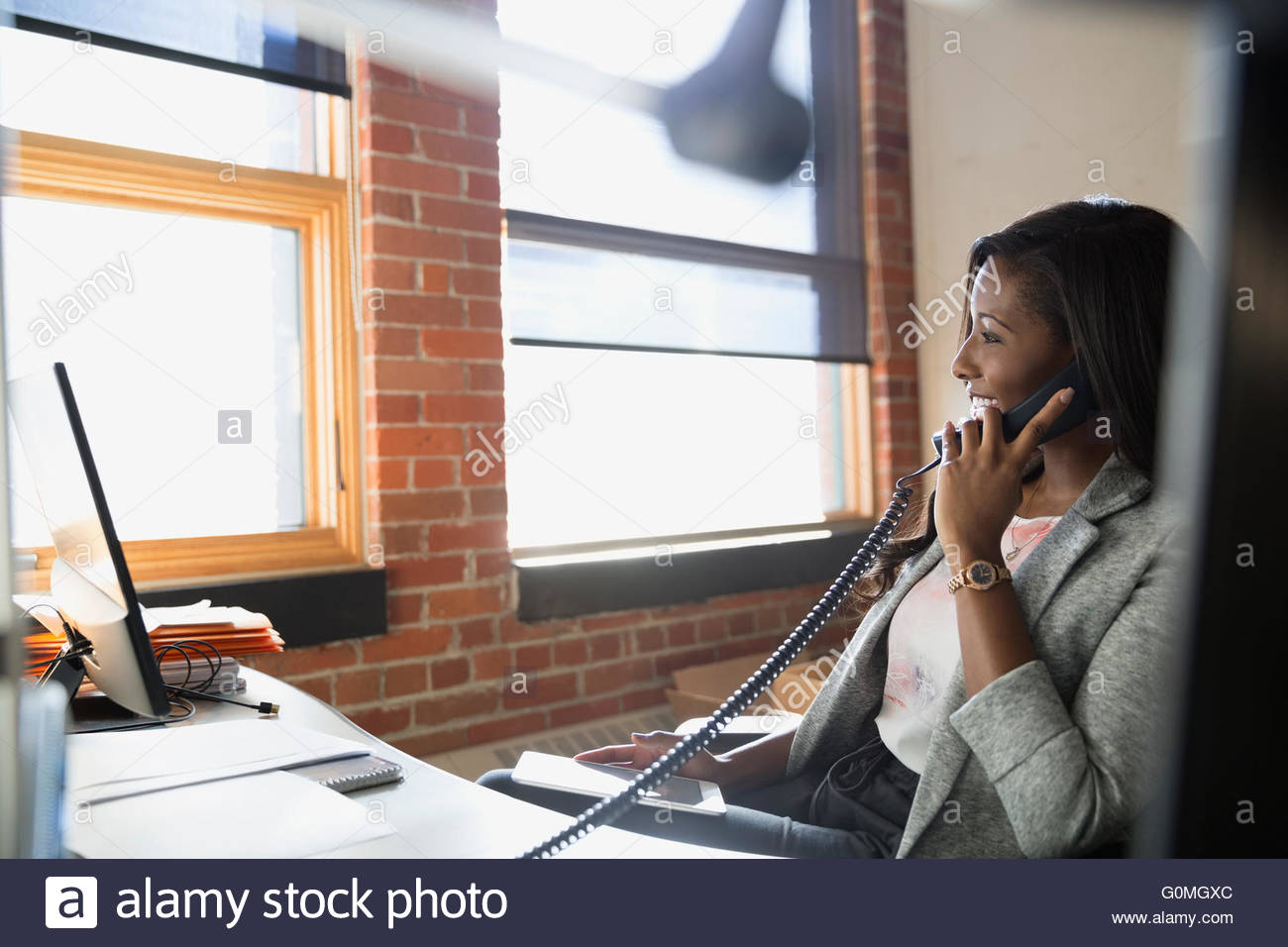 Businesswoman talking on telephone at office desk - Stock Image