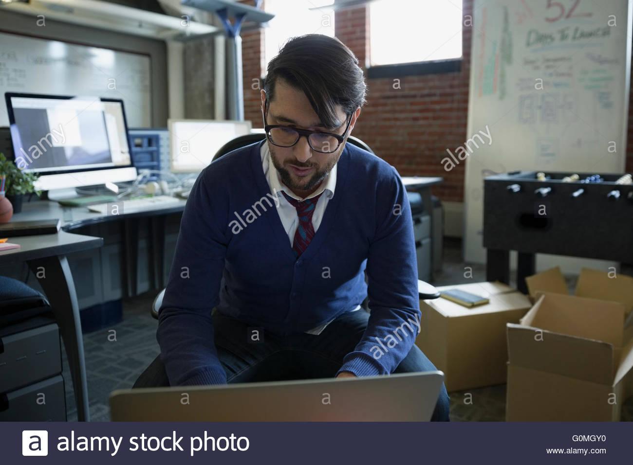 Entrepreneur using laptop in new office - Stock Image