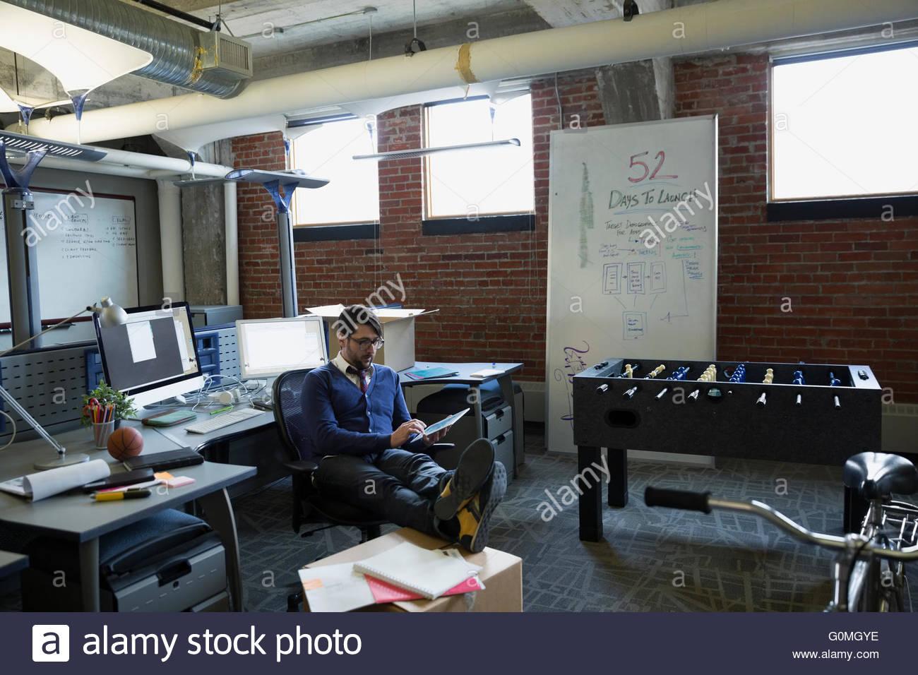 Entrepreneur using digital tablet in new office - Stock Image