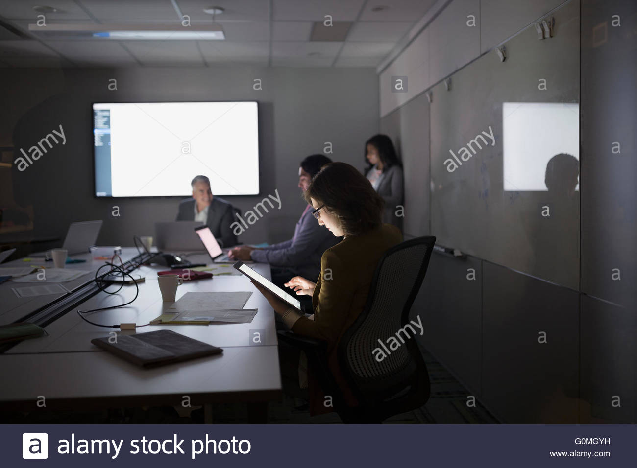 Businesswoman using digital tablet dark conference room meeting - Stock Image